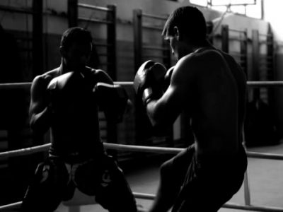 Black-and-white video of two young boxers practicing kick in ring.